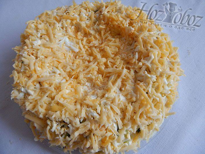 Снова перемазываем все майонезом, посыпаем тертым сыром и формируем в салате углубление