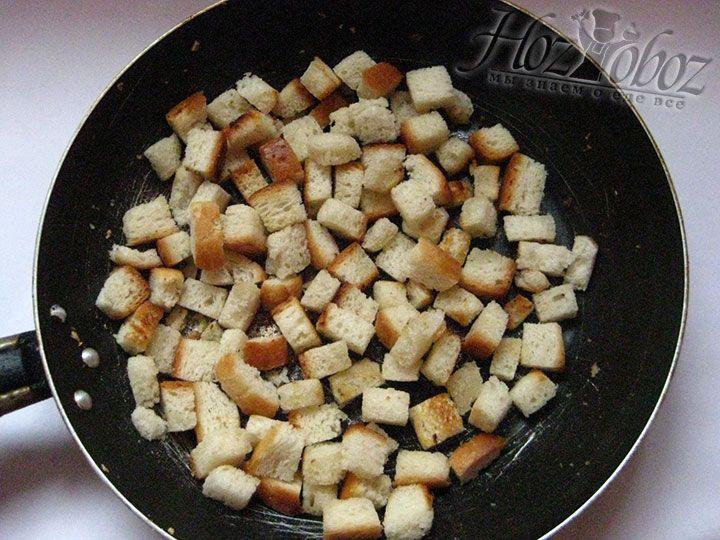 Для гренок нарезаем кубиками кусочки батона, а затем обжариваем их на растительном масле сразу после зубков чеснока. Учтите, что прежде чем добавлять хлеб, чеснок необходимо вынуть из сковороды