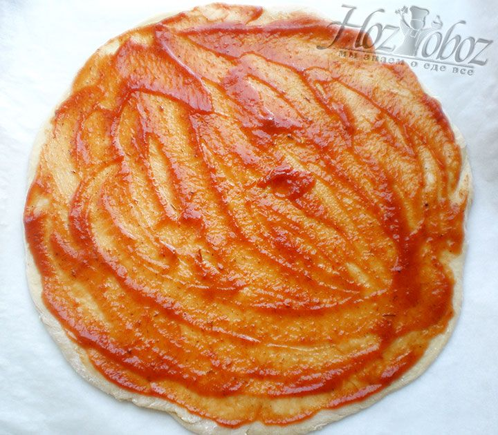 Накрываем тесто и оставляем в теплом месте для расстаивания на 1 час. Готовое тесто раскатываем в корж толщиной около 1 см, который смазываем томатный соусом