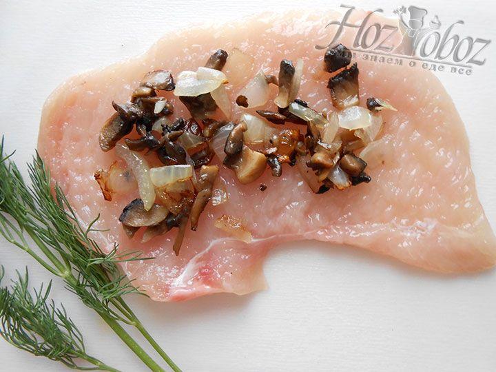 На отбитые кусочки мяса помещаем обжаренную смесь из грибов и лука