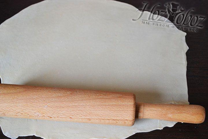 Делим тесто пополам и на посыпанной мукой поверхности раскатываем его в тонкий пласт