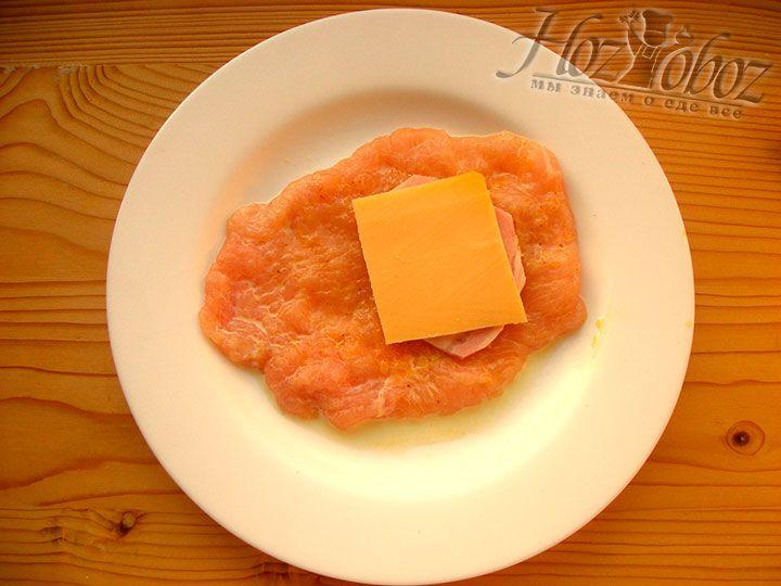 На ломтик ветчины помещаем кусочек сыра