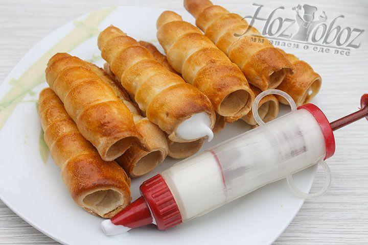 Готовые трубочки вынимаем из духовки, снимаем их с конусов и даем остыть. Затем каждое пирожное следует начинить белковым кремом и посыпать сахарной пудрой