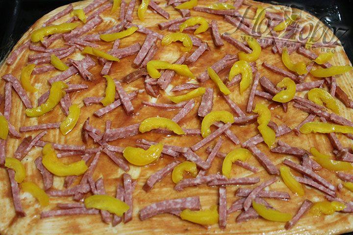 Раскладываем на корж нарезанную колбасу и перчик