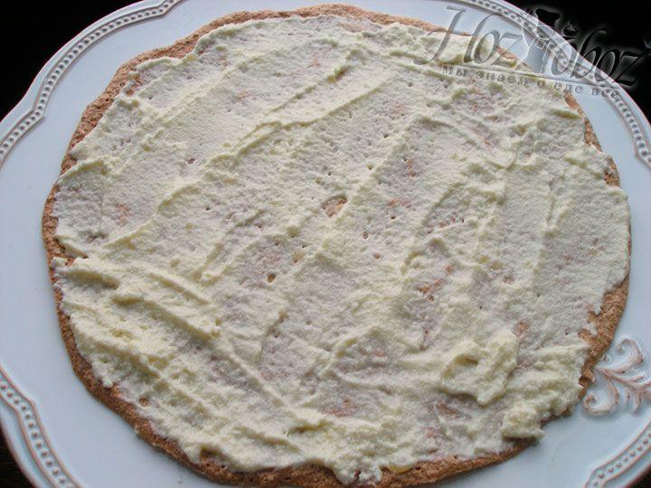 На блюдо для торта выкладываем первый корж и хорошенько промазываем его кремом