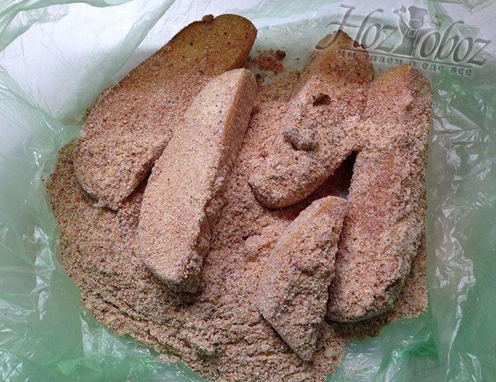 Чтобы обвалять картошку в панировке засыпаем ее по немного порциями в пакет и перетряхиваем