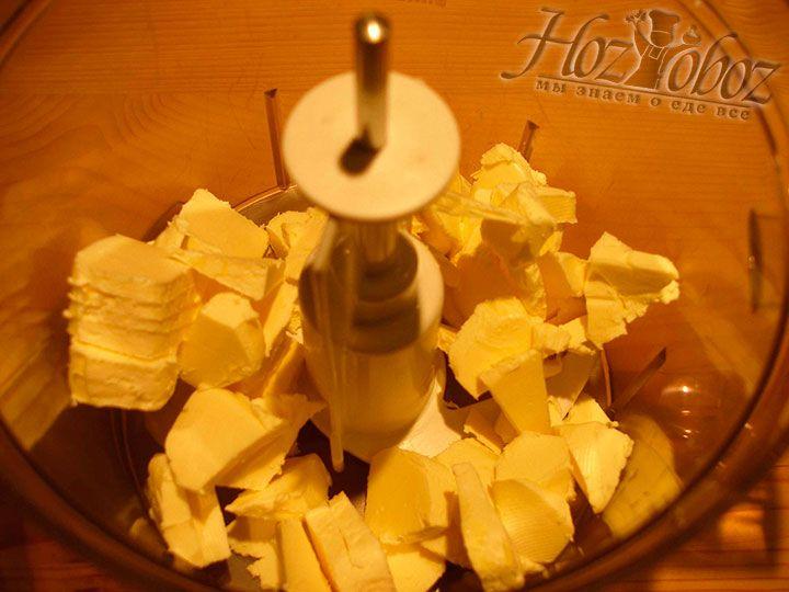 Замороженное сливочное масло насекаем небольшими кусочками и помещаем в чашу комбайна или миску