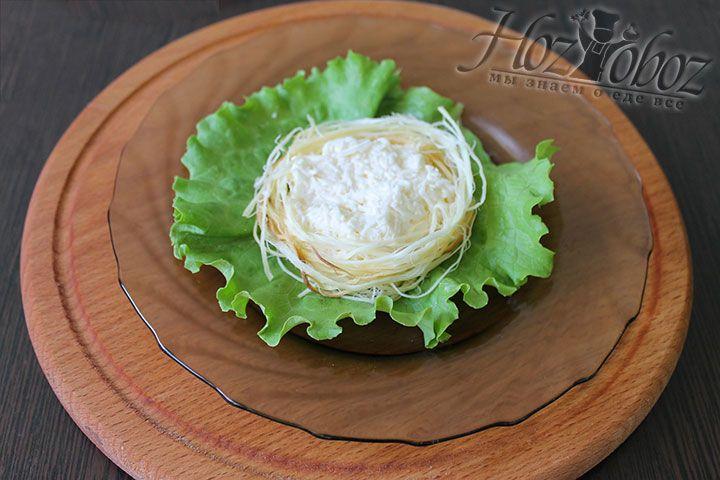 Из волокон сыра формируем пышное кольцо, которое выкладываем вокруг сырной массы тем самым придавая закуске форму гнезда