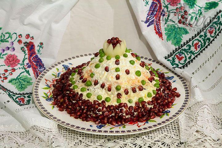 Смазываем вес салат майонезом и украшаем гранатовыми зёрнами и горошком