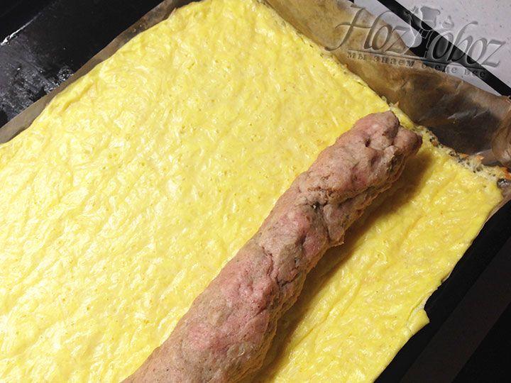 Из фарша формируем жгут и выкладываем на тесто на расстоянии около 10-15 см о края коржа