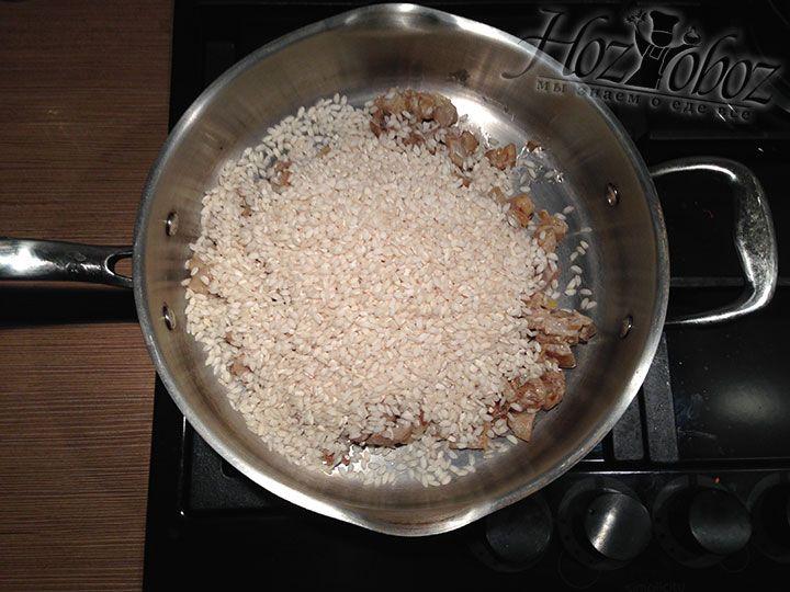В сковородку с грибами высыпаем рис и обжариваем его на оливковом масле несколько минут