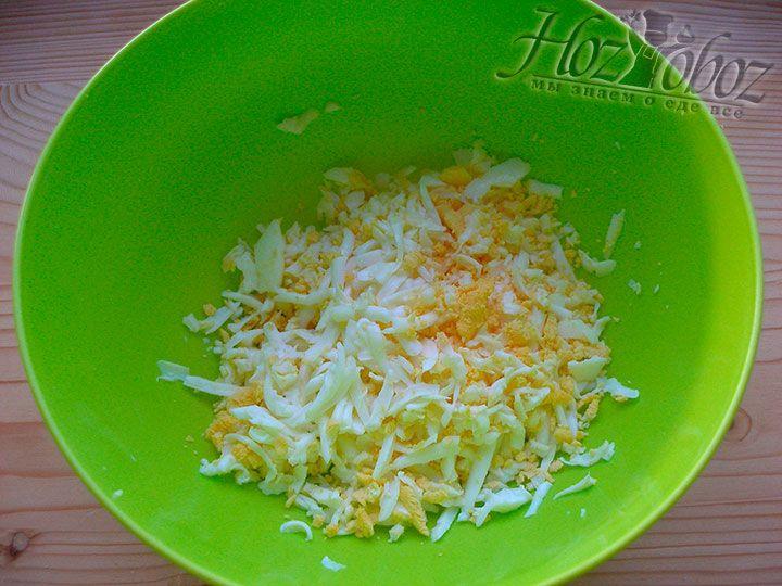 Отвариваем и натираем на крупной терке куриные яйца. Не забудем оставить желточек для украшения