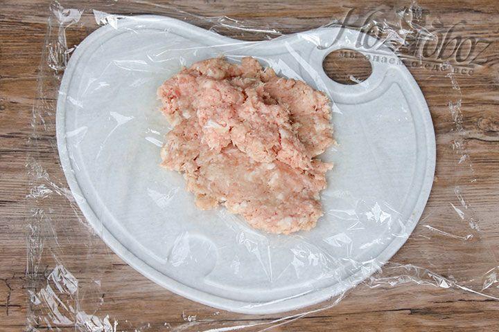 Приготовим мясной, в нашем случае куриный, фарш, которому затем придадим форму круга с помощью пищевой пленки