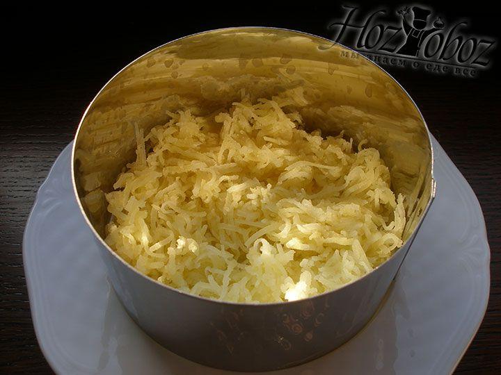 Для оформления салат будем выкладывать его в формовочное кольцо и в качестве первого слоя используем натертый мелко картофель