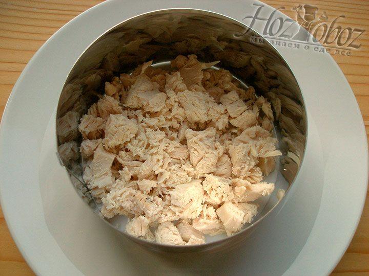 В формовочное кольцо выкладываем первым слоем салата половину куриного филе