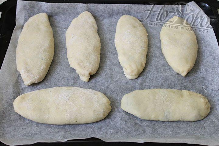 Готовые пирожки поместите на противень устланный пергаментом и смазанный растительным или сливочным маслом