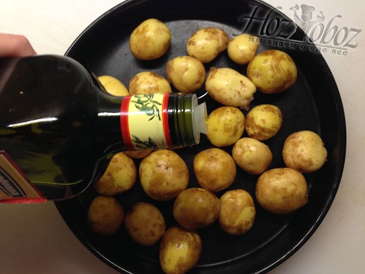 Вымытую картошку помещаем в глубокий противень для запекания и поливаем оливковым маслом