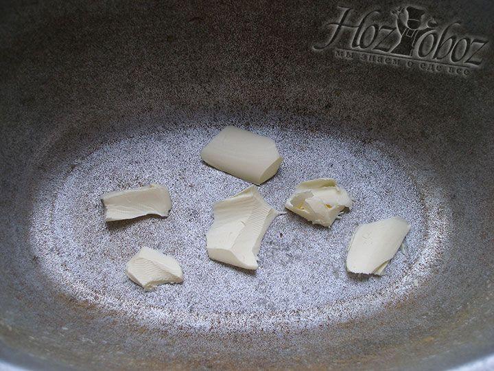 На дно жароупорной кастрюли для запекания выкладываем немного сливочного масла