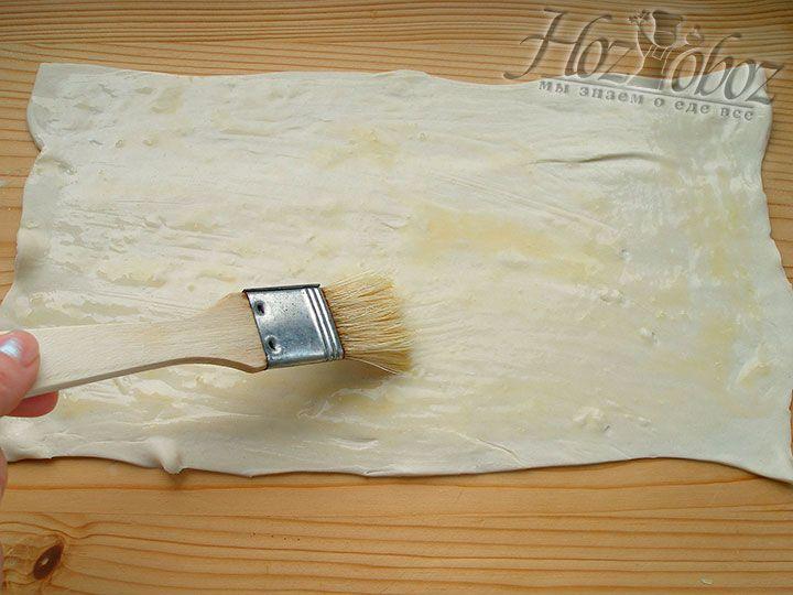Очень тонко раскатываем слоеное тесто и смазываем его яичной смесью