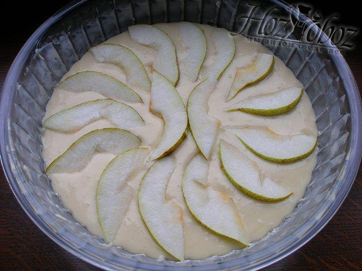Форму для выпечки смазываем сливочным маслом, перекладываем в нее тесто и выкладываем сверху дольки груш
