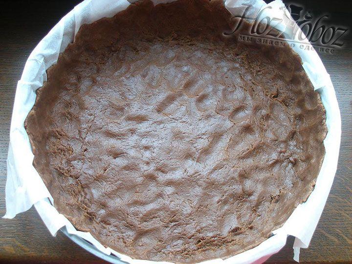 Форму для выпекания пирога устилаем пергаментной бумагой и вручную распределяем на ней основу для пирога с бортиками