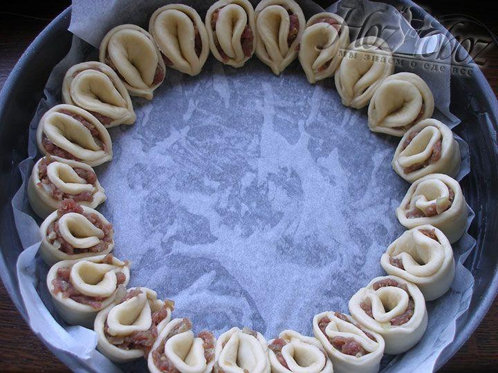 Форму для выпечки диаметром примерно 30 см устилаем пергаментом и смазываем сливочным маслом. Затем по кругу помещаем в нее готовые лепестки с мясом
