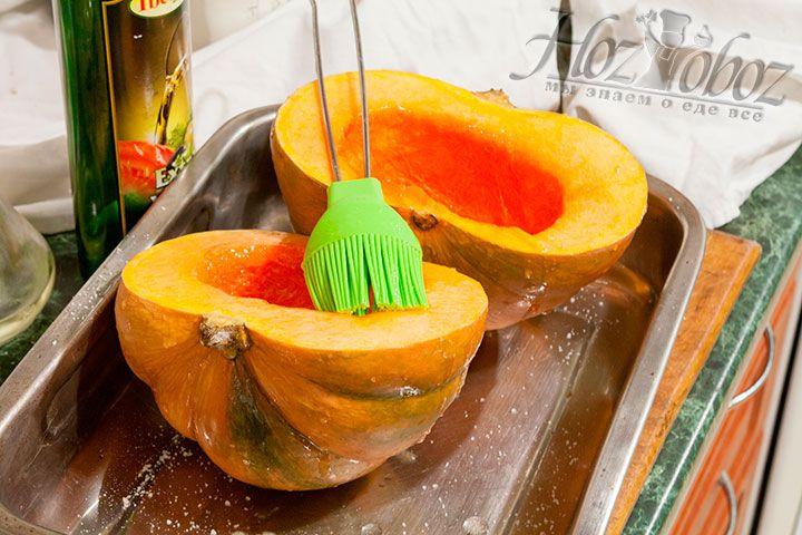 Подсоленные половинки тыквы смажем оливковым маслом и поставим запекать при температуре 200 градусов примерно на 30 минут