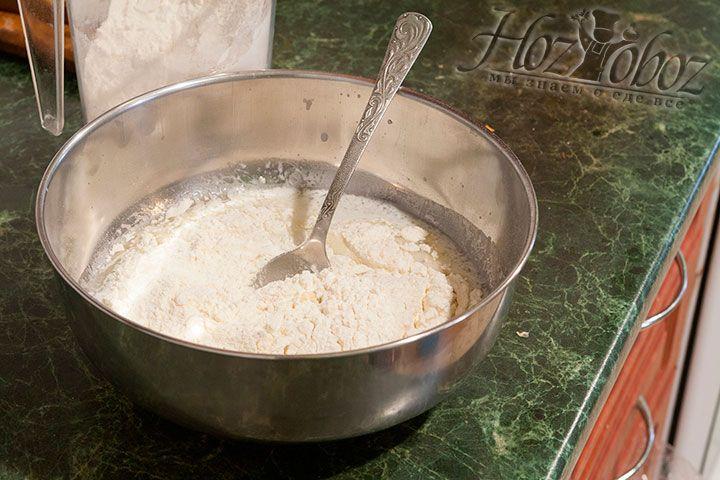 Теперь просеиваем в миску пшеничную муку и начинаем замешивать тесто ложкой