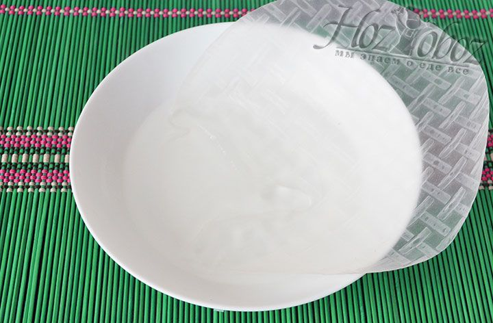 Подготовим основу для блинов. Для этого в миску нальем теплую воду и опустим в нее листы рисовой бумаги начиная от края. Когда размокнет край постепенно опускаем в воду весь лист, но делать все следует быстро чтобы рисовое тесто не прилипло к рукам