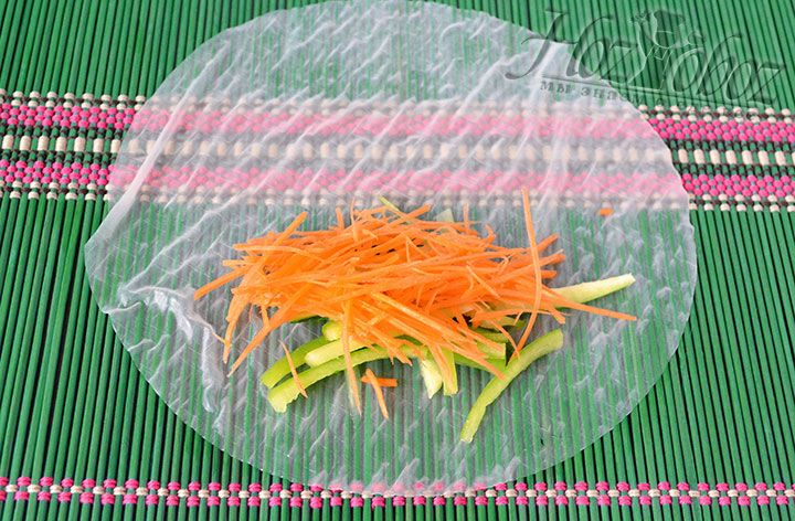 Чтобы избавится от лишней влаги готовую, уж мягкую рисовую бумагу, помещаем на циновку или полотенце. Теперь быстро выкладываем ближе к нижнему краю часть овощной начинки. Не медлите иначе рисовая бумага просто раскиснет
