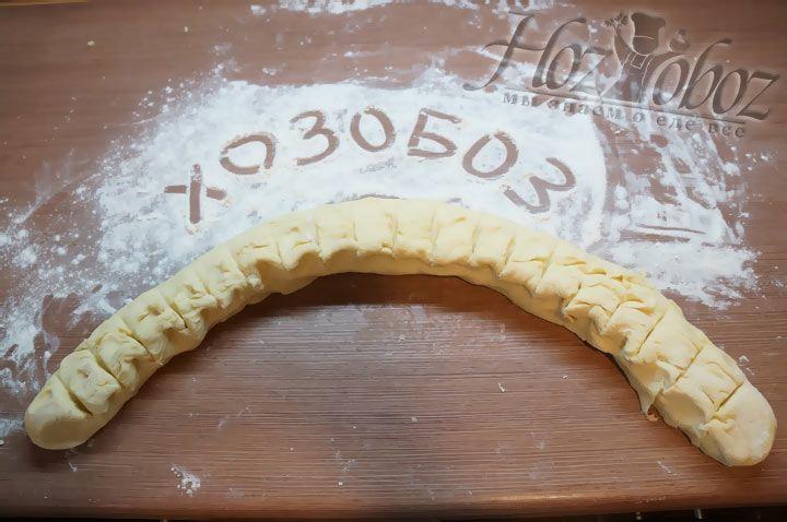 Тесто скатываем как на фото и придаем ему форму змейки и размечаем заготовки толщиной 3 см