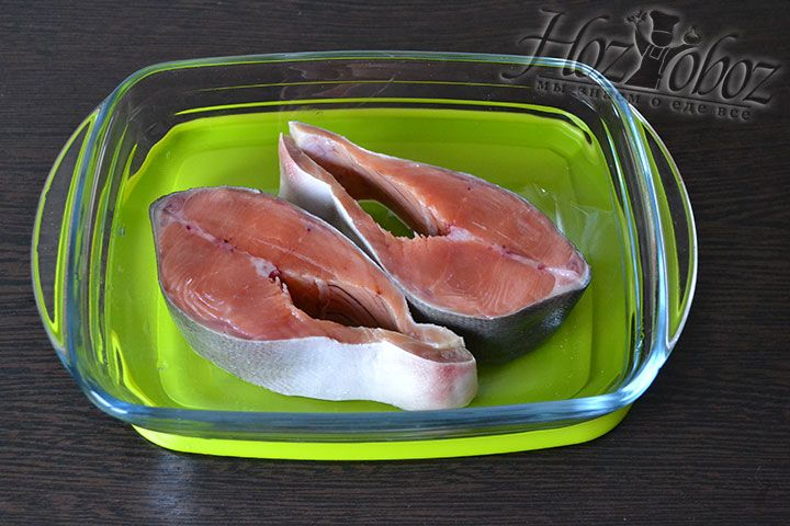 Очищенную рыбу разрезаем ножом на две части и отправляем на противень с бортами