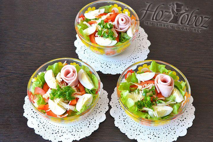 Ветчину скручиваем розочками и добавляем в салат в качестве украшения. Сюда же пойдет дополнительная порция зеленого лука и тертого сыры