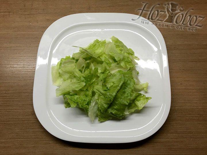 Просушенные листы салата разорвем на кусочки и сформируем «подушку» для будущего салата