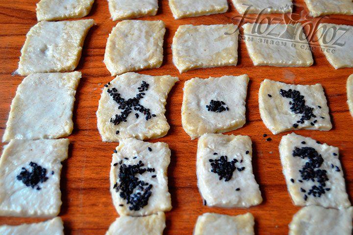 Присыпьте основу крекеров большим количеством черного или белого кунжута