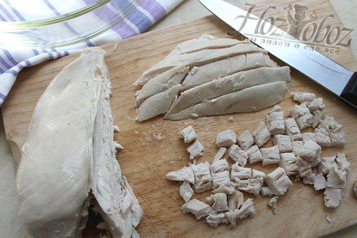 Для оформления салата первым слоем выкладываем на тарелку нарезунную кубиком куриную грудку