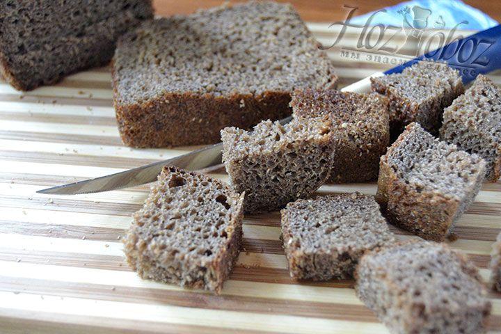 Подготовьте основу для приготовления сухарей, нарезав ржаной хлеб маленькими кусочками