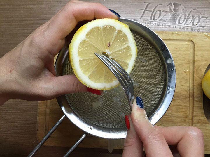Разрезаем лимоны по очереди поперек на две части и на сито выжимаем из каждой половины сок