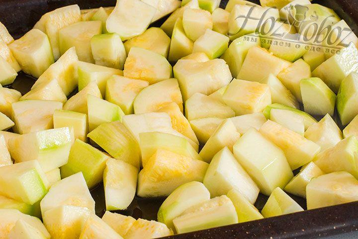 Молодые кабачки просто нарезаем кубиками, а более зрелые очищаем от кожуры и семян после чего тоже нарезаем. Выкладываем нарезанные овощи на противень, поливаем столовой ложкой растительного масла и запекаем 30 минут в духовке при температуре 180 градусов