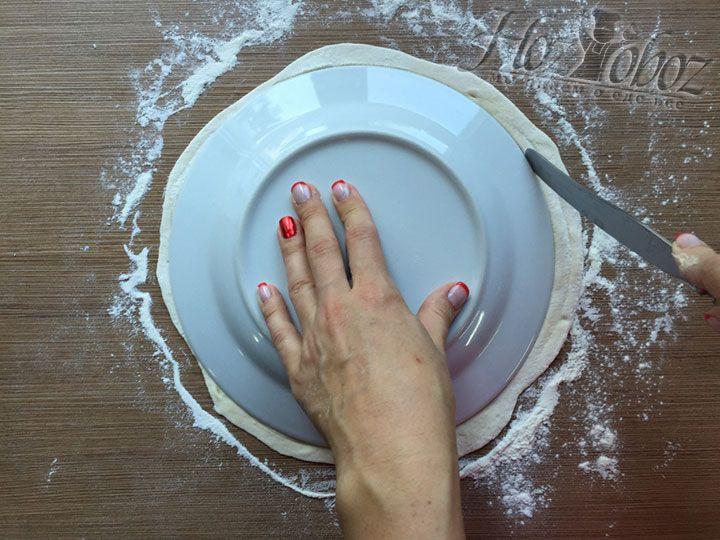 Обрезаем лишнее тесто вокруг тарелки и делаем заготовки для чебуреков