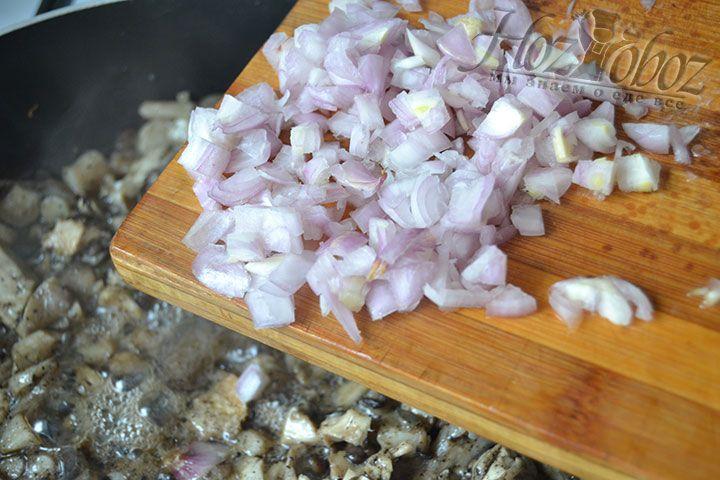 Нарежьте мелко лук и высыпьте его в сковороду с грибами