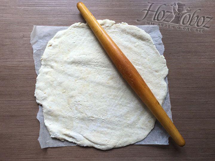 Чтобы раскатать основу для пирога, воспользуйтесь двумя листами пергамента и поместите тесто между ними