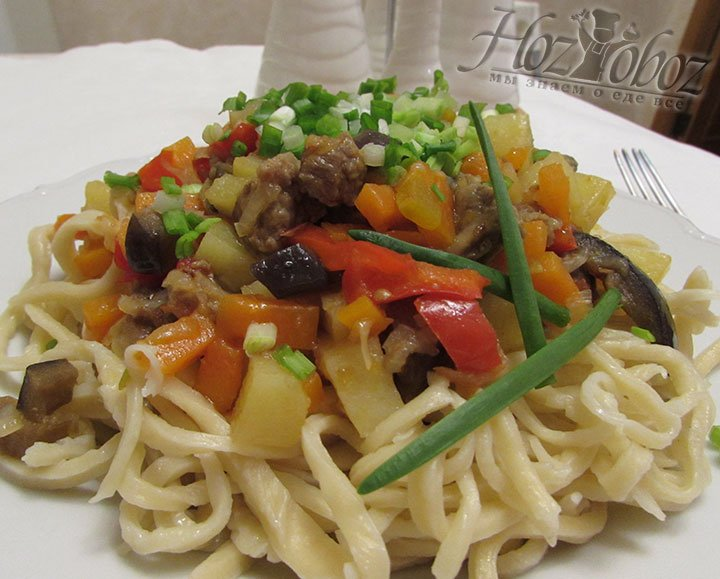 Выкладываем лагман на тарелку. Начинаем с лапши, потом тушеные овощи и в конце нарезанный зеленый лук