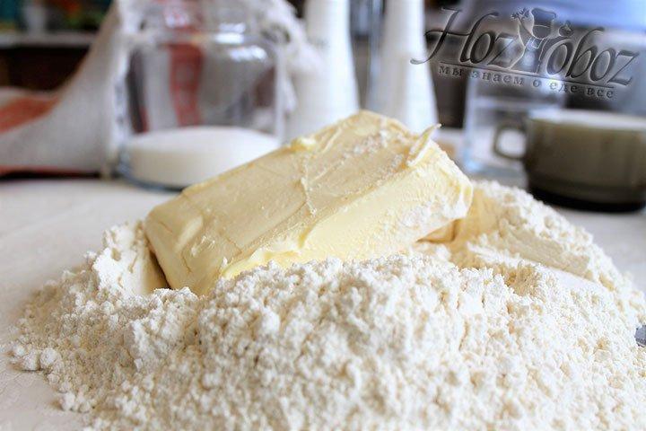 Прежде всего замесим тесто, а для этого горкой насыпем на стол муку и поместим внутрь кусочек сливочного масла
