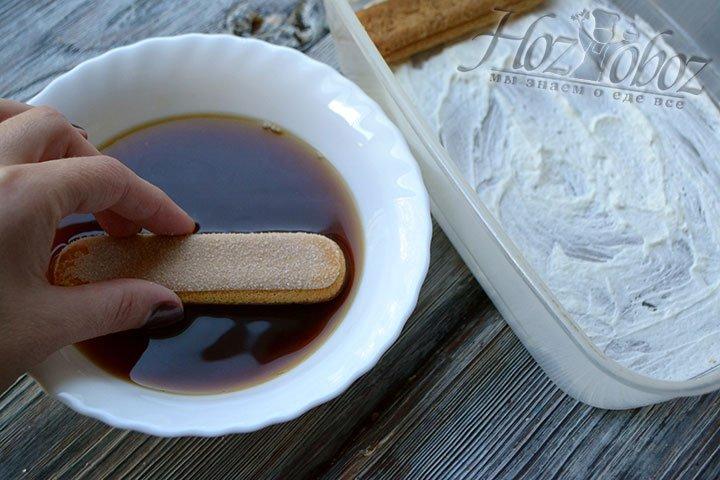 Завариваем немного натурального кофе и остужаем его до комнатной температуры. Тем временем дно формы для Тирамису смазываем кремом, а палочки Савоярди пропитываем кофе. Пропитанное печенье следует поместить в крем пропитанной стороной вверх