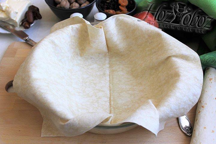 На дно смазанной формы выкладываем лист тонкого армянского лаваша и заворачиваем кончики по краям