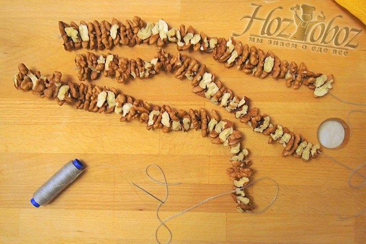 С помощью иглы и нитки подготовим бусы из орехов и оставим их сохнуть на сутки