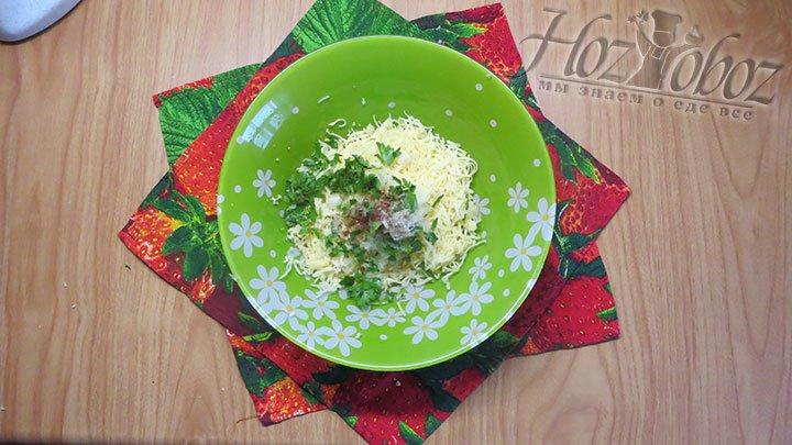 В глубокую миску натираем помельче сыр, а затем добавляем соль, специи, чеснок и рубленную зелень