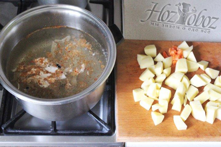 4Клубни картофеля чистим и нарезаем кубиками, а очищенную морковь натираем на терке, после чего отправляем овощи в бульон