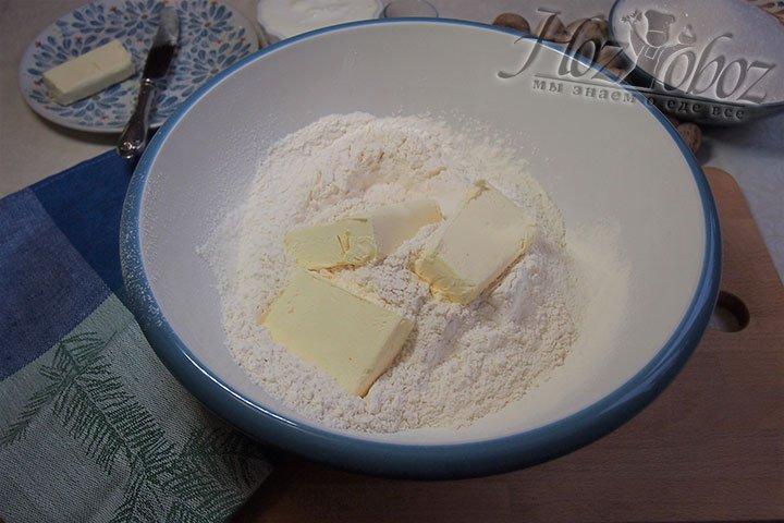 Масло разделим на части и выложим в просеянную муку